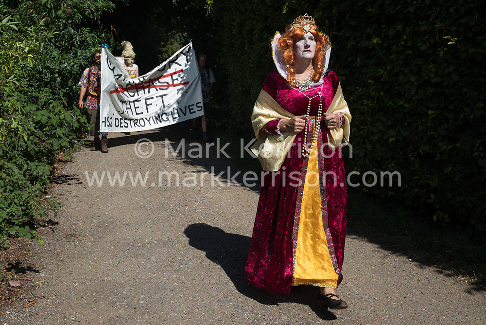 Harefield, UK. 31st July, 2020. Environmental activists in period costume from groups opposed to the HS2 high-speed rail link restage a historical 1602 visit by Queen Elizabeth I to Dews Farm. The activists tried to retrace the steps of Queen Elizabeth I from St Mary's church to Dews Farm in order to pay their respects to Anne and Ron Ryall, 73 and 72, on the day of their eviction from Dews Farm by HS2 after having spent nine years and their life savings renovating their £1m dream home, but found their path blocked by HS2 fences and security guards.