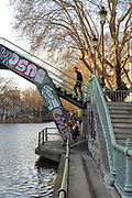 Passerelle Richerand, a steel pedestrian footbridge in the Marais basin, over the Canal Saint-Martin in the 10th arrondissement of Paris, France. The Canal Saint-Martin is a 4.6km long waterway between the Canal de l'Ourcq and river Seine, built 1802-25 to provide a fresh water source to the city and provide a trade route for canal barges. Picture by Manuel Cohen
