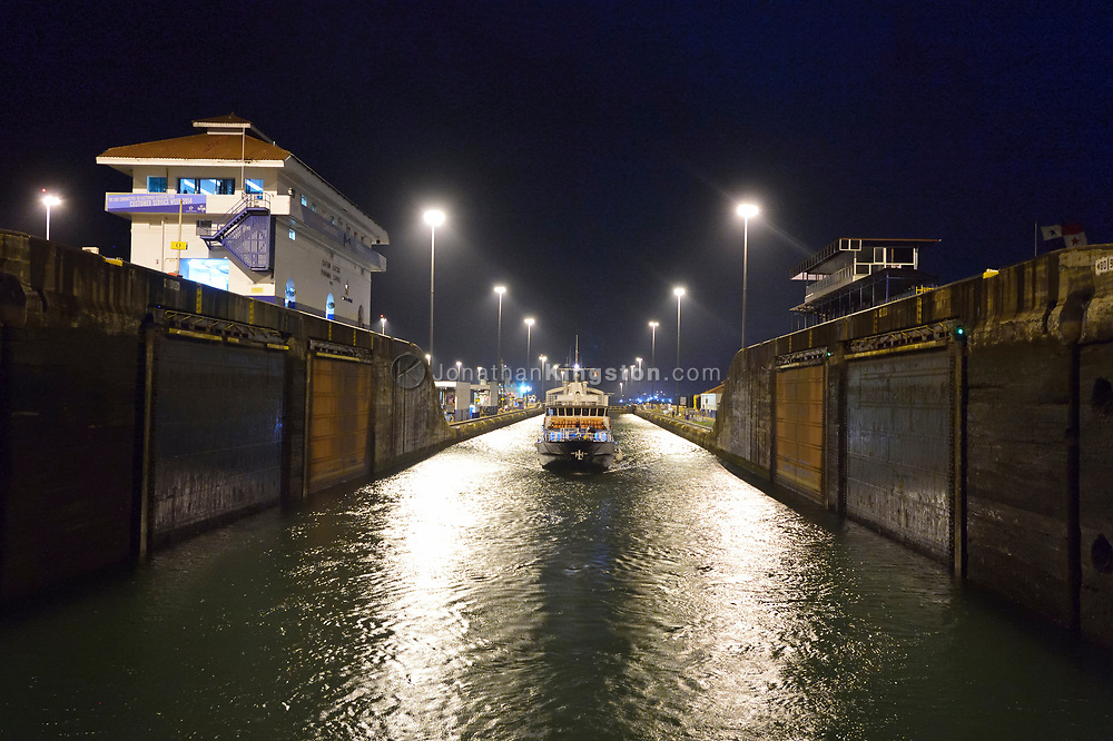 A small passenger ship enters the Gatun locks at night, on the Atlantic side of the Panama Canal, Panama.