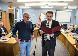 Laconia Daily Sun reporter Michael Kitch listens as Laconia Mayor Ed Engler reads a proclamation marking Kitch's 14 years of covering the Laconia city council on Monday, April 24, 2017.  (Alan MacRae for the Laconia Daily Sun)