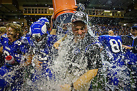 Coeur d'Alene High head coach Shawn Amos receives a celebratory drenching from his players during the closing seconds of the Viking's 28-7 win over Centennial High in the 5A State Championship Friday at the University of Idaho Kibbie Dome. The state title is the first for the Vikings in 25 years.