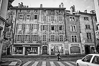 Black and white view of colorful, historic buildings found along the Thiou Canal, in Old Town Annecy, France.