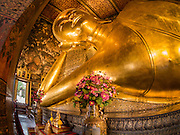 11 AUGUST 2016 - BANGKOK, THAILAND:  The famous reclining Buddha statue at Wat Pho. Wat Pho (the Temple of the Reclining Buddha), is formally known as Wat Phra Chetuphon. It's one of the largest temple complexes in Bangkok and best known for the giant reclining Buddha that measures 46 metres long and is covered in gold leaf. There is also a large ordination hall and the best known massage school in Thailand on the temple grounds.        PHOTO BY JACK KURTZ