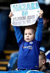 A young fan in the stands holds up a sign asking for Chelsea's Eden Hazard's shirt