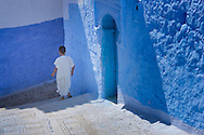 Boy walking down an alley in the medina of Chefchaouen, Morocco.