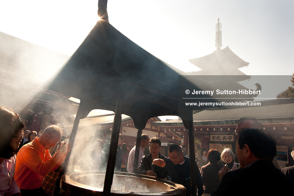 Visitors waft incense smoke over themselves to cure ailments, pains and illness, at Senso-ji Temple, in Asakusa district of Tokyo, Japan, Monday 7th November 2011.