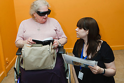 Staff with visually-impaired wheelchair user consulting diary.