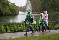 © licensed to London News Pictures. London, UK 09/05/2013. A family walking under the rain in St James's Park in London on Thursday, 09 May 2013. Photo credit: Tolga Akmen/LNP