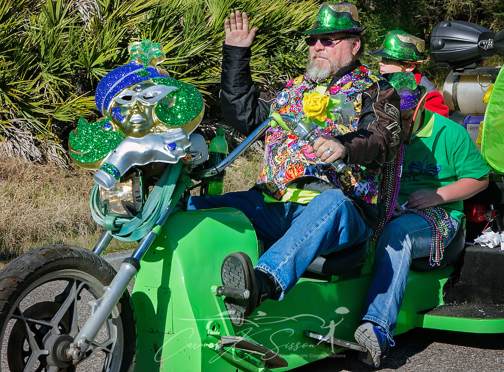 A biker waves to the crowd as he rides down Bienville Boulevard in Dauphin Island's first People's Parade during Mardi Gras, Feb. 4, 2017, in Dauphin Island, Alabama. French settlers held the first Mardi Gras in 1703, making Mobile's celebration the oldest Mardi Gras in the United States. The first parade of the season is traditionally held on Dauphin Island and draws thousands. (Photo by Carmen K. Sisson/Cloudybright)
