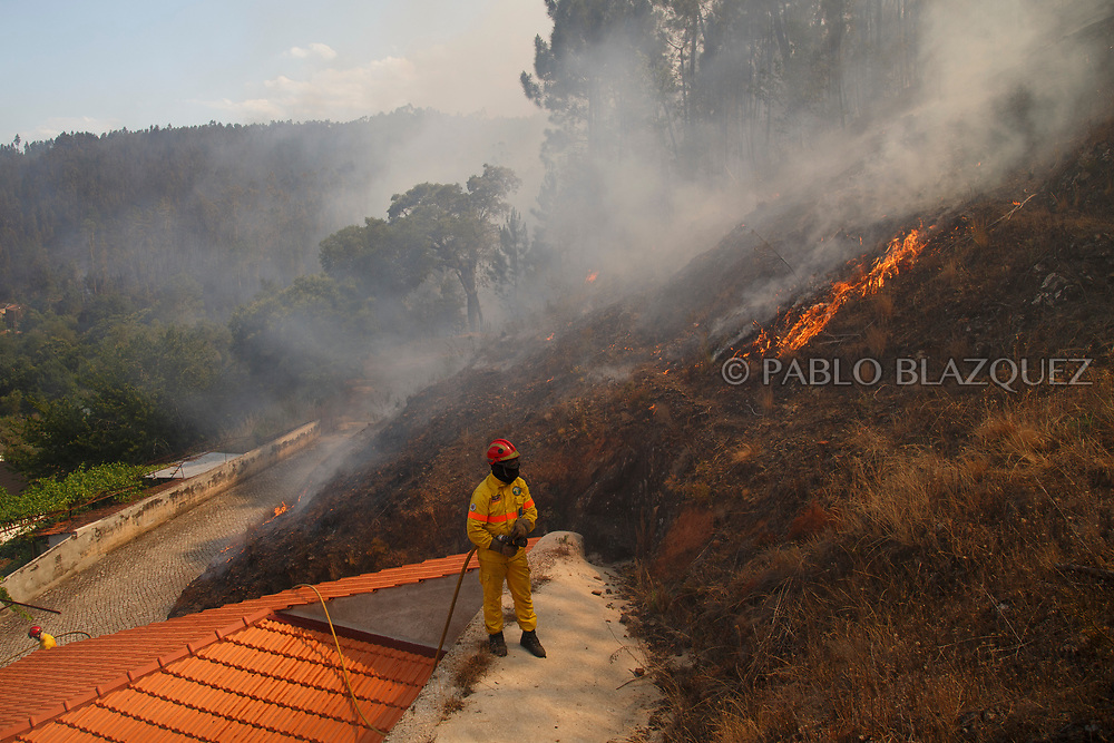 LEIRIA, PORTUGAL - JUNE 20:  A firefighter watches flames approaching to Mega Fundeira village after a wildfire took dozens of lives on June 20, 2017 near Picha, in Leiria district, Portugal. On Saturday night, a forest fire became uncontrollable in the Leiria district, killing at least 62 people and leaving many injured. Some of the victims died inside their cars as they tried to flee the area.  (Photo by Pablo Blazquez Dominguez/Getty Images)
