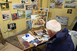 Artist at work in side antiques market at  Barras Market in Gallowgate Glasgow, United Kingdom