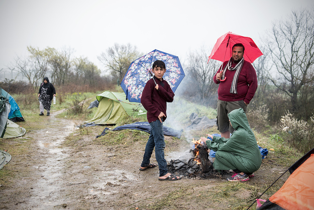 A Kurdish family from Syria trying to warm up in Idomeni. They have been waiting for the past 25 days for the border to open. <br /> <br /> Thousands of refugees are stranded in Idomeni unable to cross the border. The facilities here are stretched to the limit and the conditions are appalling. It's raining, it's cold there is mud everywhere and there is no hope that the border will open anytime soon.