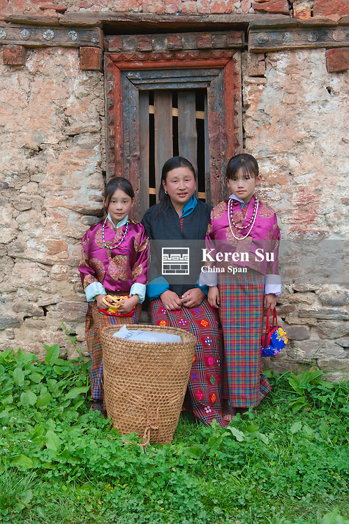 Portrait of farmer girls with basket in front of brick house, Bumthang, Bhutan
