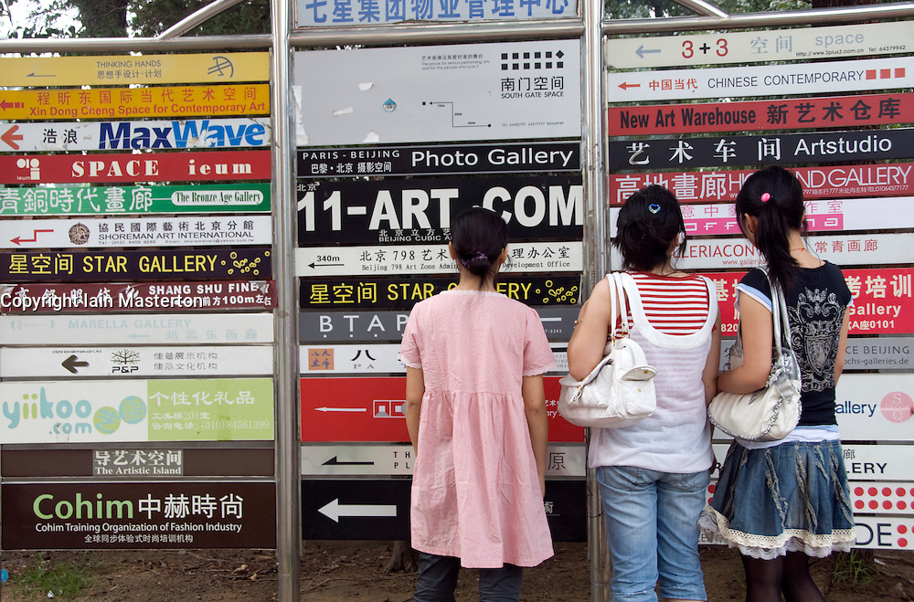 Visitors looking at gallery information signs at new 798 Art District in beijing