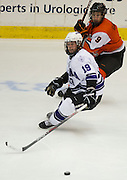 2012/03/16 - RIT forward Matt Garbowsky and Niagara forward Dan Baco chase a puck during the Atlantic Hockey semifinal at the Blue Cross Arena in Rochester, N.Y. on March 16th, 2012. RIT defeated Niagara 2-1 in overtime.