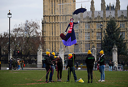 © Licensed to London News Pictures. 06/01/2017. London, UK. Members of a Greenpeace team help to suspend an image of Mary Poppins wearing a face mask in front of Big Ben during a Greenpeace protest about air pollution in Parliament Square, London. Photo credit: Ben Cawthra/LNP