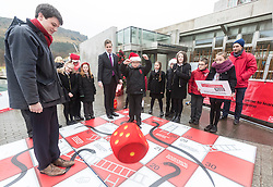 """Campaigners from Shelter Scotland raise awareness of their campaign """"Homelessness - Far From Fixed"""" outside the Scottish Parliament in Edinburgh. They are joined by carol singers from Corstorphine Primary School, a Christmas tree and a giant snakes and ladders board game - Chance Not Choice - which illustrates how life chances affect people's ability to keep a roof over their head.<br /> <br /> Pictured:Daniel Johnson from Scottish Labour playing Chance Not Choice with Evan Jones from Costorphine Primary School throwing the dice"""