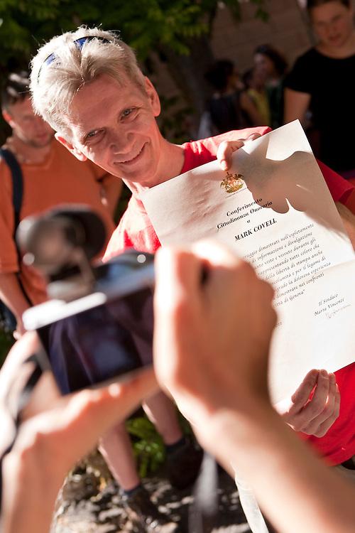Commemorazione di Carlo Giuliani in Piazza Alimonda a Genova. Mark Cowell, giornalista/media attivista britannico, nel 2001 fu aggredito dalle forze di polizia davanti alla scola Diaz (notte tra il 21 e il 22 luglio 2001). Venne ferito gravemente: fu dichiarato dai sanitari codice rosso, ovvero paziente a rischio di vita. Ancora chiede giustizia (il processo a chi lo ha massacrato non è ancora giunto all'ultimo grado di giudizio). Nell'immagine mostra a una fotografa l'attestato di cittadinanza onoraria che il comune di Genova gli ha consegnato.