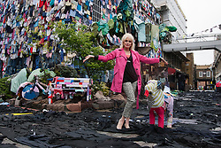 © licensed to London News Pictures. London, UK 26/04/2012. Joanna Lumley posing in a street covered with clothes from walls, the road, and the pavement to a fabric-strewn bench, car and even a dog to illustrate future uses for old clothes in Brick Lane. M&S will be accepting people's old and unwanted clothes for their charity campaign with Oxfam. Photo credit: Tolga Akmen/LNP