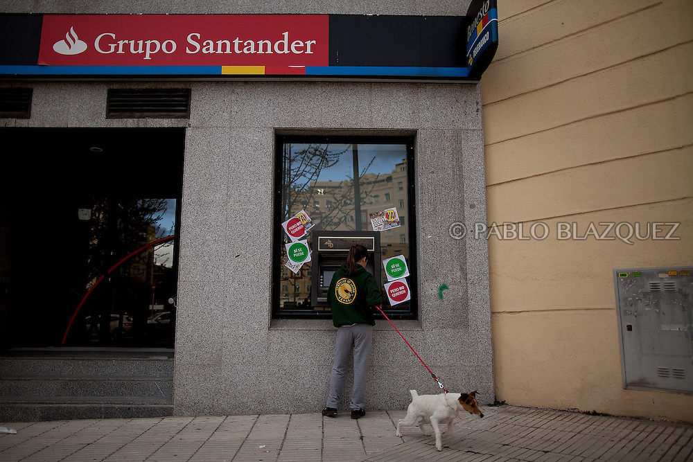 A woman holding a dog uses a cash machine with stickers reading 'Yes we can, but they don't want' after an 'escrache' outside the house of PP deputy Beatriz Rodriguez Salmones on April12, 2013 in Madrid, Spain. The Mortgage Holders Platform (PAH) and other anti evictions organizations have been organizing 'escraches' for several weeks under the slogan 'There are lives at risk' to claim the vote for a Popular Legislative Initiative (ILP) to stop evictions and facilitate social rent, outside Popular Party deputies' houses and offices. 'Escraches' are a form of peaceful protest that were used in Argentine in 1995 to publically denounce pardoned members of the dictatorship for their crimes at their doorsteps.