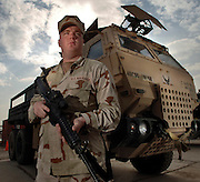 Airman 1st Class Kevin Ingerick, combat convoy operator stands ready with his M-4 Carbine and one of the many armor modified M-1083 Medium Tactical Vehicles that he has used for combat escort of supply convoys. Ingerick was deployed with the 732nd Expeditionary Logistics Readiness Squadron at Balad Air Base, Iraq. For meritorious service during an ambush, was awarded the Bronze Star with Valor and the Army Commendation Medal. He is a native of Snow Camp, NC.  (U.S. Air Force photo by Master Sgt. Lance Cheung)