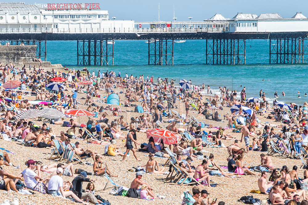© Licensed to London News Pictures. 30/05/2020. Brighton, UK. Groups of more than 6 people can be seen on the beach in Brighton and Hove as thousands of members of the public take to the seaside on the hottest day of the year so far.  Photo credit: Hugo Michiels/LNP