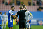 Referee Gavin Ward shows a yellow card to Wigan Athletic midfielder Sam Morsy (5)  and Derby County midfielder Harry Wilson (7) during the EFL Sky Bet Championship match between Wigan Athletic and Derby County at the DW Stadium, Wigan, England on 8 December 2018.