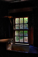 Photograph of an old sink with light coming through a window.