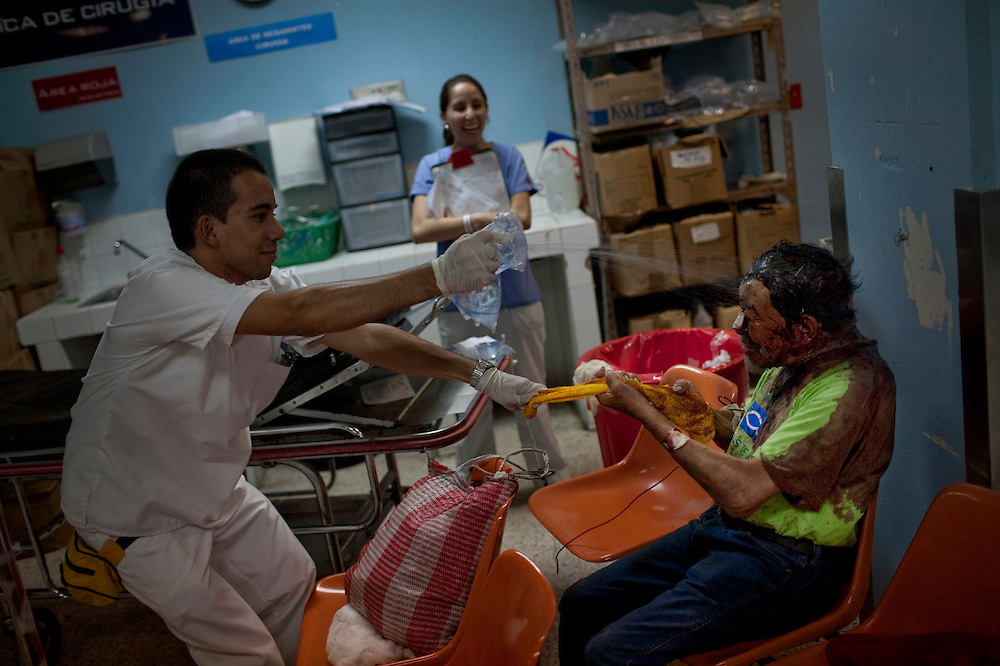 A student throws water to a patient who refuses to clean his wounds in the emergency room of the the San Juan de Dios hospital, Guatemala City, Friday, June 11, 2010. (AP Photo/Rodrigo Abd)