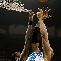 February 1, 2011; New Orleans, LA, USA; Washington Wizards power forward Andray Blatche (7) gets his finger caught in the net while going up for a rebound with New Orleans Hornets power forward David West (30) during the second quarter at the New Orleans Arena.   Mandatory Credit: Derick E. Hingle