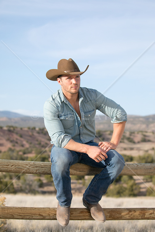 cowboy relaxing on a split rail fence