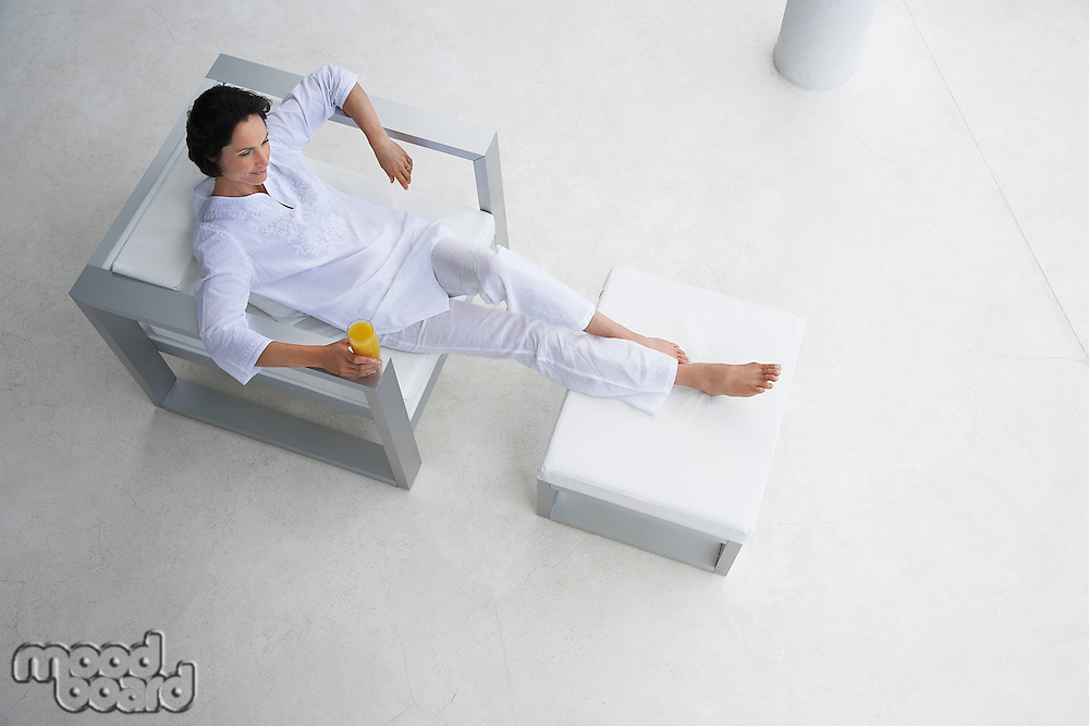 Woman holding glass of juice reclining in armchair elevated view