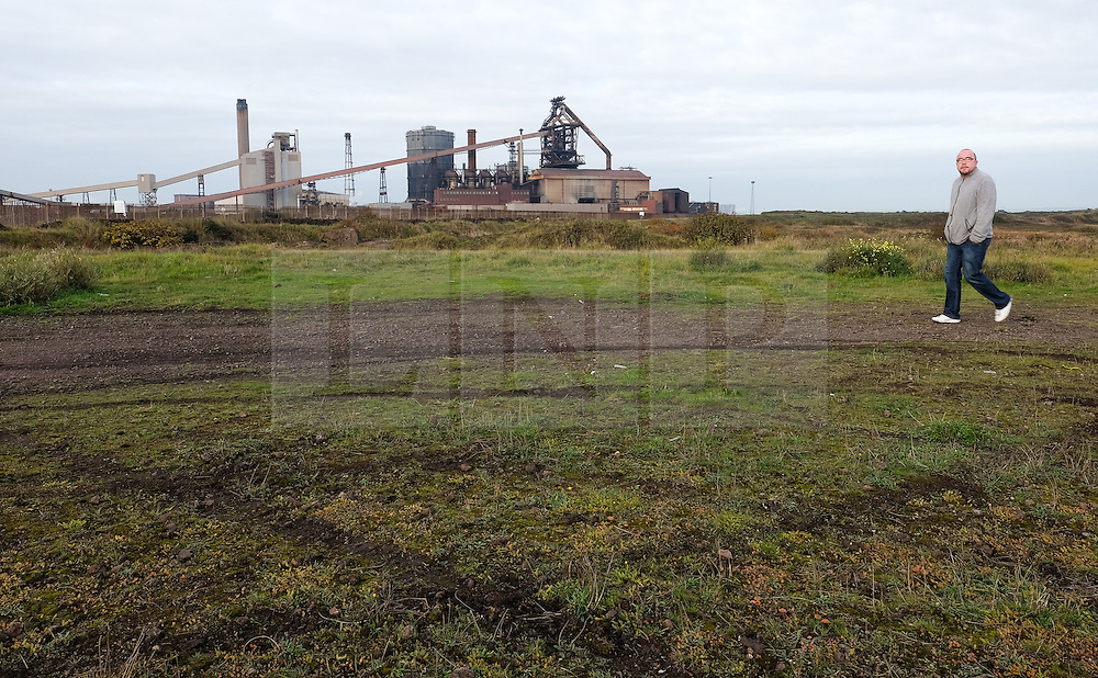 © Licensed to London News Pictures.20/10/15<br /> Redcar, UK. <br /> <br /> A man walks over waste ground in front of the recently closed SSI UK steel blast furnace in Redcar, England. The closure of the site marks the end of 170 years of steel making heritage on Teesside and was the first of a number of recent closures of steel making plants across the UK.<br /> <br /> Photo credit : Ian Forsyth/LNP