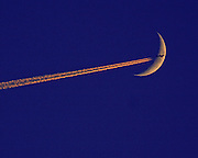 An optical illusion of a plane at high altitude passing the moon.