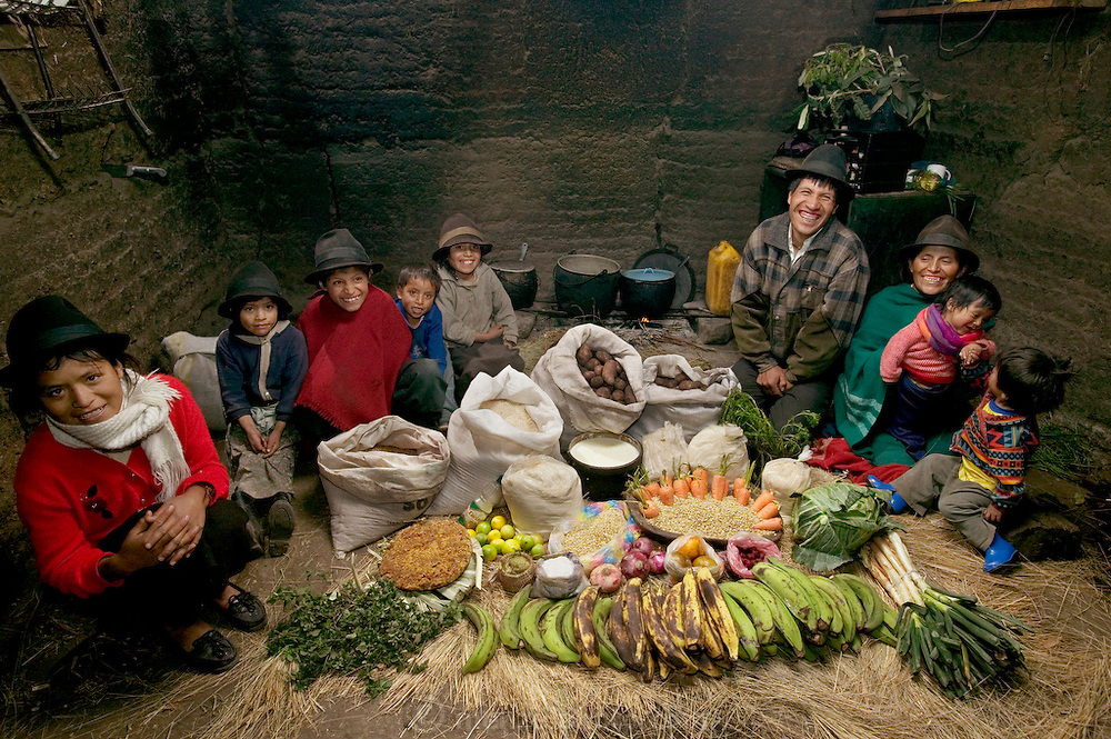 (MODEL RELEASED IMAGE). The Ayme family in their kitchen house in Tingo, Ecuador, a village in the central Andes, with one week's worth of food. Ermelinda Ayme Sichigalo, 37, and Orlando Ayme, 35, sit flanked by their children (left to right): Livia, 15, Natalie, 8, Moises, 11, Alvarito, 4, Jessica, 10, Orlando hijo (Junior, held by Ermelinda), 9 months, and Mauricio, 30 months. Not in photograph: Lucia, 5, who lives with her grandparents to help them out. Cooking method: wood fire. Food preservation: natural drying. /// The Ayme family is one of the thirty families featured in the book Hungry Planet: What the World Eats (p. 106). Food expenditure for one week: $31.55 USD. (Please refer to Hungry Planet book p. 107 for the family's detailed food list.)