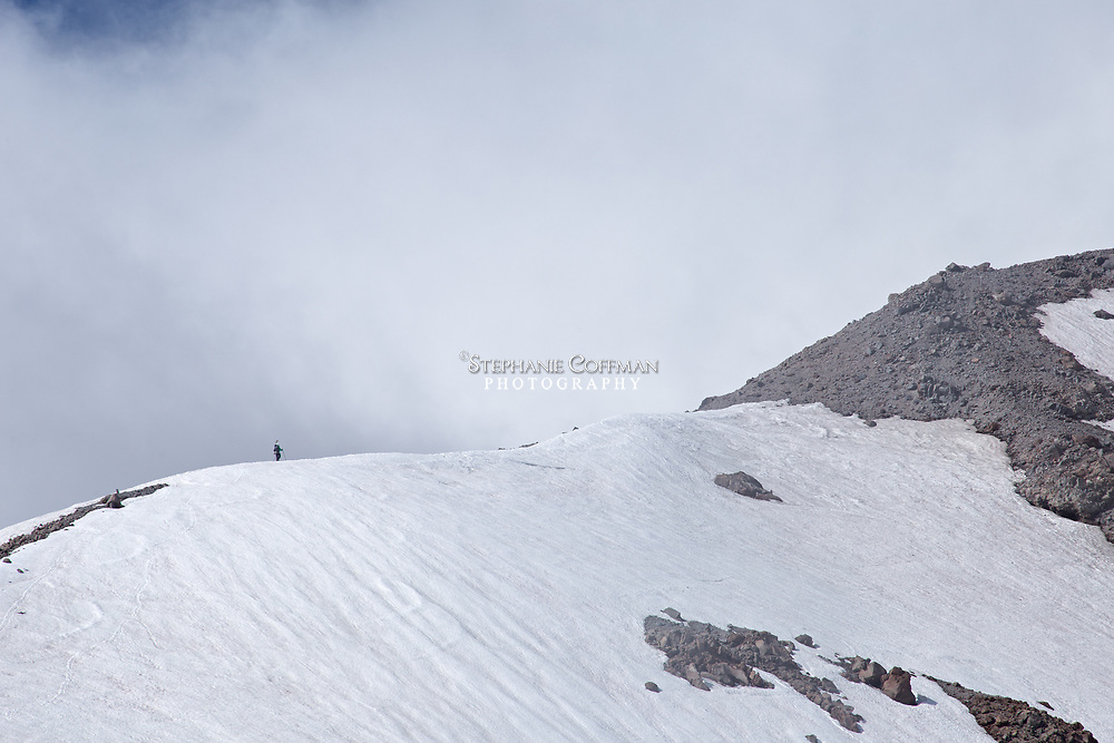 A snowboarder hiking the ridgeline along the Cooper Spur trail to the top of Mt. Hood, Oregon, USA