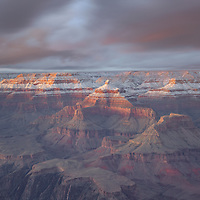 Sunset light on snow covered cliffs of Grand Canyon National Park, AZ