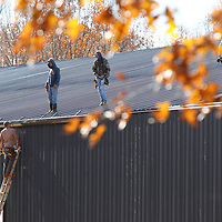Workers with Carpenter Contractors in Mantachie, work on installing gutters along the roofline of the new Eight Days of Hope Headquarters in Pontotoc on Monday. Carpenter has overseen the construction of the building.