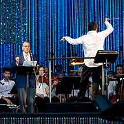"""July 13, 2013 - New York, NY : Joe Torre, standing at left, Alan Gilbert, standing at right, <br /> and The New York Philharmonic perform  Ernest Thayer's """"Casey at the Bat"""" in the free MLB All-Star Charity Concert to benefit Hurricane Sandy victims, in Central Park's great lawn on July 13, 2013. Pop star Mariah Carey (not pictured) also made a guest appearance. <br /> CREDIT: Karsten Moran for The New York Times"""