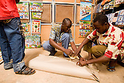 Vendors wrap an item that was just bought by a customer at the 22nd Salon International de l'Artisanat de Ouagadougou (SIAO) in Ouagadougou, Burkina Faso on Saturday November 1, 2008.