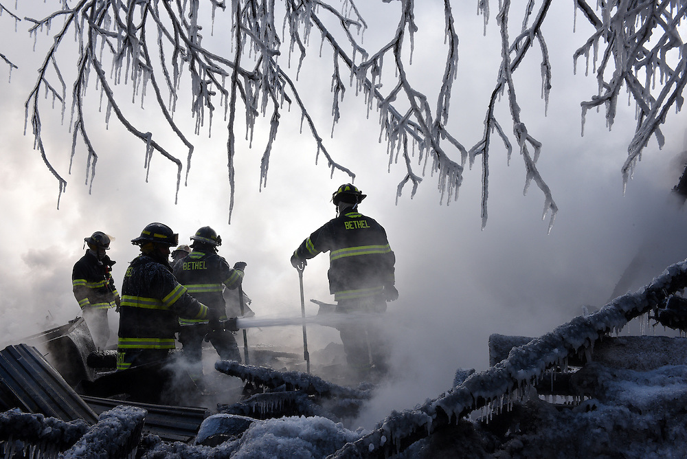 Bethel firefighters work to extinguish any remaining embers inside the destroyed home of Arlene St. Pierre in Bethel Vermont, Friday, Feb. 13, 2015. Bethel, Randolph, Randolph Center and Barnard fire departments responded to the scene at about 8 a.m. Friday when the house and barn were already engulfed in flames. (Valley News - James M. Patterson)<br /> Copyright &copy; Valley News. May not be reprinted or used online without permission. Send requests to permission@vnews.com.