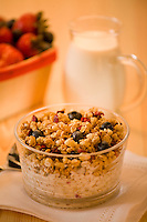 Granola in clear glass bowl with milk,in glass pitcher , glass bowls with spoons on white lucite,