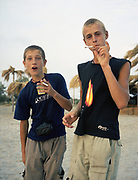 Two young boys standing on sand smoking cigarettes.
