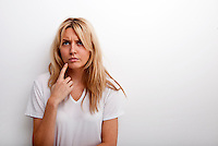 Thoughtful woman standing against white background