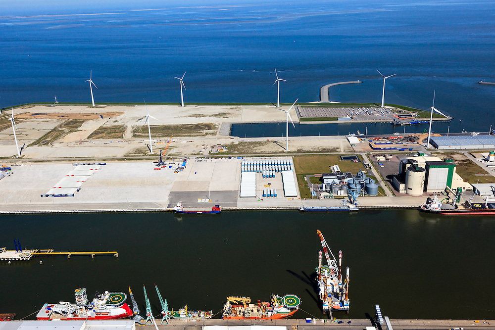 Nederland, Groningen, Eemshaven, 01-05-2013; de Julianahaven, overzicht,  opslag en assemblage van onderdelen van offshore windturbines, zoals wieken (rotorbladen), masten, turbines. Op de  windcarrier met helikopterdek de wieken van een windmolen..De firma Fred. Olsen Windcarrier is verantwoordelijk voor transport, installatie en onderhoud van offshore wind parken. Waddenzee op de achtergrond. .Port of Eemshaven: storage and assembly of components for offshore wind turbines in the Julianahaven at Eemshaven. .Fred. Olsen Windcarrier company provides innovative and tailored services for the transport, installation, and maintenance of offshore wind parks, such as wings (blades), masts, turbines. On the wind carrier with helicopter deck the sails of a windmill. Wadden Sea at the back. .luchtfoto (toeslag op standard tarieven).aerial photo (additional fee required).copyright foto/photo Siebe Swart