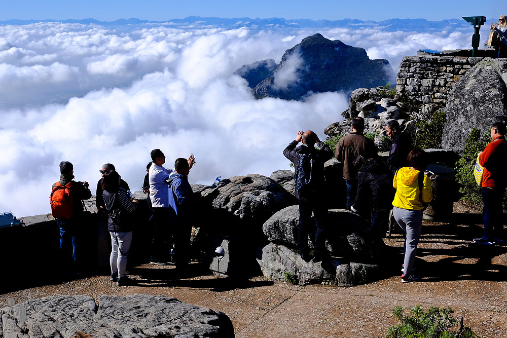 Cape Town, South Africa. Above the clouds. Tourists enjoy the view from the top of Table Mountain with a blanket of clouds below.