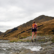 A female runner crosses Moke Creek on the Ben Lomond High Country Station during the Pure South Shotover Moonlight Mountain Marathon and trail runs. Moke Lake, Queenstown, New Zealand. 4th February 2012. Photo Tim Clayton