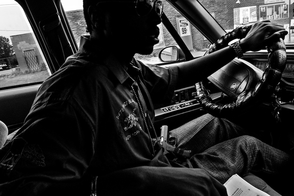 Ryan keeps his handgun on his lap while driving through  Gary, Indiana.  As a matter of course, many in Gary carry handguns for personal protection. There has been a spate of murders in Gary late in the summer.   (© William B. Plowman/Redux)