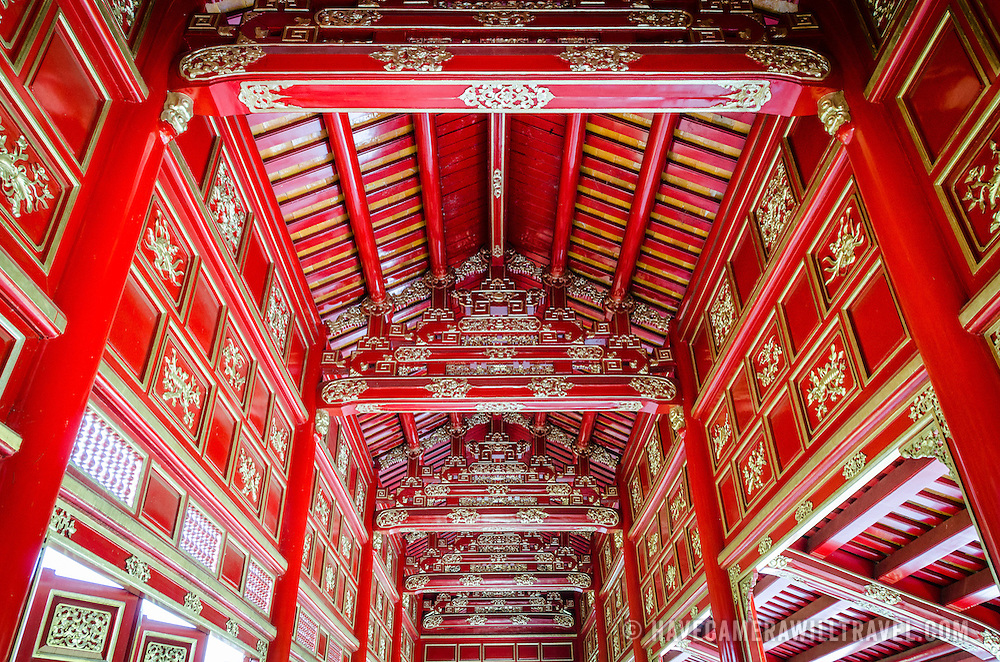 Bright red ceiling rafters in a restore building at the Imperial City in Hue, Vietnam. A self-enclosed and fortified palace, the complex includes the Purple Forbidden City, which was the inner sanctum of the imperial household, as well as temples, courtyards, gardens, and other buildings. Much of the Imperial City was damaged or destroyed during the Vietnam War. It is now designated as a UNESCO World Heritage site.