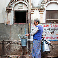 A Chai Tea Sellers with Milk and Tea Containers Hanging On His Bicycle in Varanasi, India
